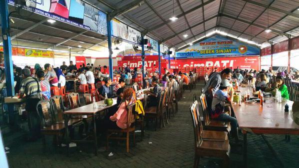 Suasana di restoran Nasi Bebek Sinjay, Bangkalan. Pengunjung berbagi tempat dengan pengunjung lainnya di meja panjang yang berjejer.