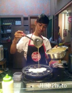 Pemilik Tomodachi, Yanuar Ariyanto, memasak takoyaki di gerainya yang ada di Pajang, Laweyan, Solo. Foto diambil belum lama ini. (Istimewa)